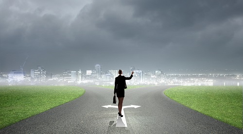 Back view of businesswoman standing on crossroads and making cho